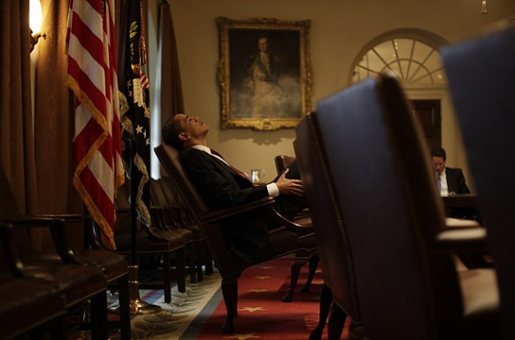 obama sitting at his chair and brooding oval office