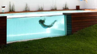 Elevated swimming pool with glass walls for Glass swimming pool walls cost