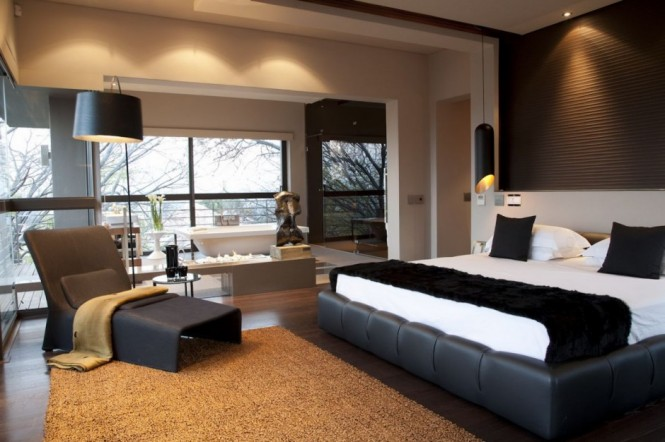 The master bedroom is also surrounded by floor-to-ceiling windows, with the branches of the trees almost poking into the room. The design is luxurious and inviting, yet modern. Soft and fuzzy materials combined with a neutral color palette make the design of this room truly comfy and bedroom-appropriate.