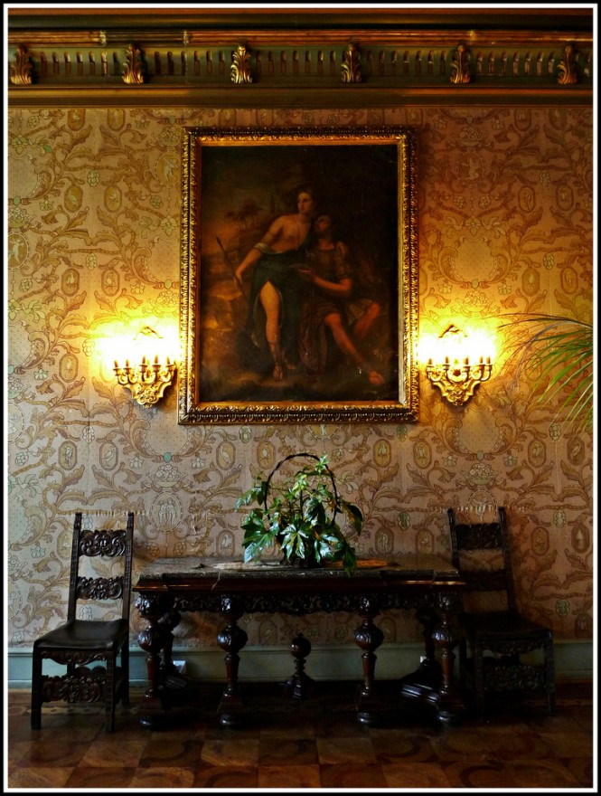 The heavy, dark wood with its intricate, ornate carvings,  is a prime example of castle furniture. The richly adorned wallpaper, wall candles, and medieval-era painting add to the castle theme.  Photo Credit