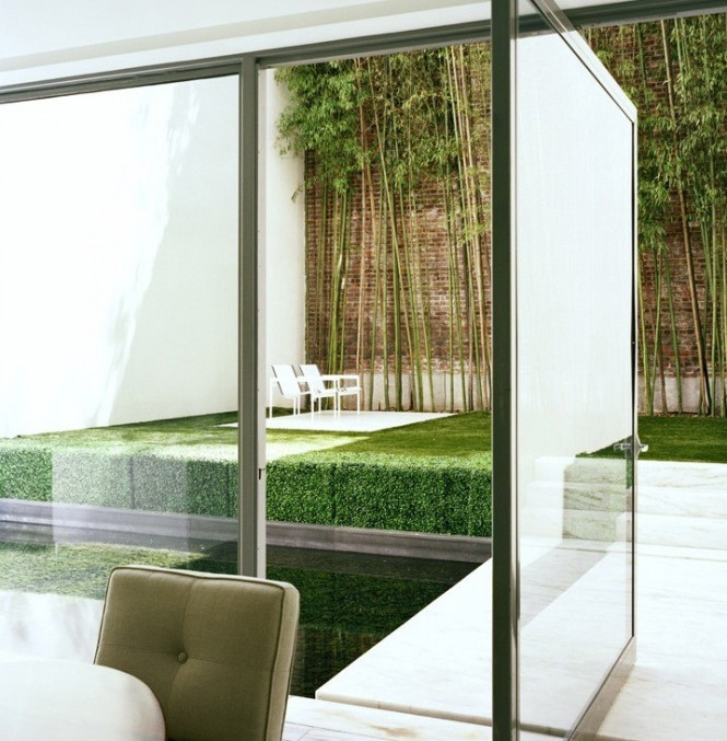 Here, we get a taste of the ultra-modern in a NYC apartment backyard. The glass paneled doors, offer an unobstructed view of the small backyard, so it offers a design element to the room even if one is simply sitting in the living area.