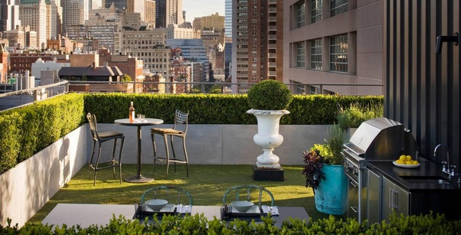 This rooftop is reminiscent of a palace garden, with large stone plant pots and perfectly manicured shrubbery.
