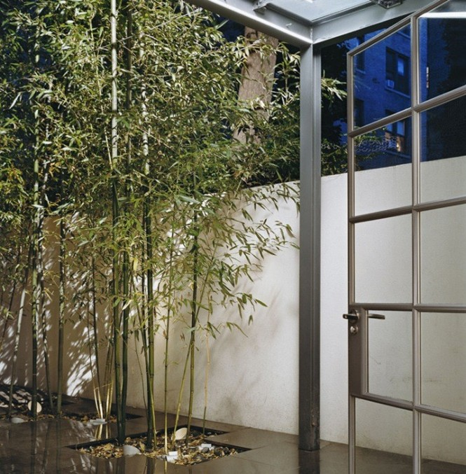 This courtyard has a marble tiled floor and thin trees popping out from them. It is another interesting way to incorporate the idea of melding the indoor and outdoor world together to create a more comfortable, homey garden environment.