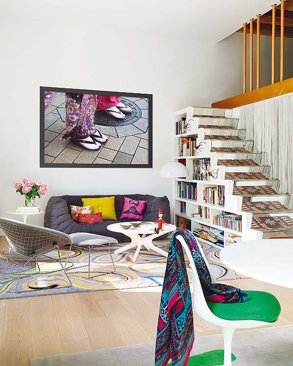 The swirling design in the rug is reminiscent of Gaudi's swirling mosaics in Park Guell. The decor is colorful, vibrant, yet modern. The bookshelves under the stairs are a wonderful and fun space-saver.