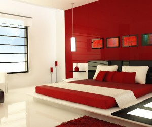 Design by Zaib. This ultra modern red bedroom, is accessorized with light panels, unique red vases, and hanging vertical lights. The intensity of the red and brown colors are relieved by the cream colored pillows and floors.
