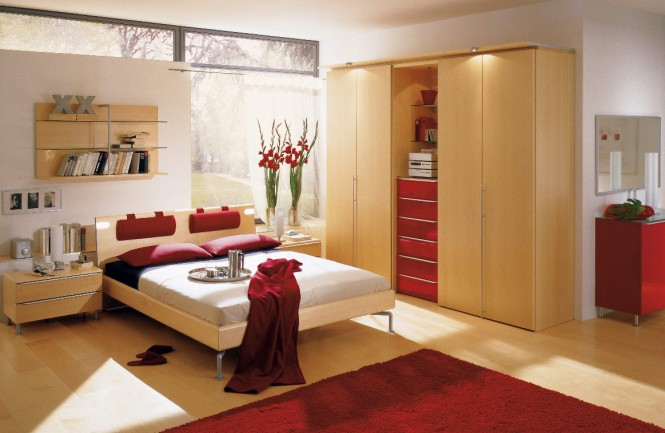 Design by Hulsta. We admire the soft wood that permeates most of this red bedroom. The red here, only appears in a few pops, in the carpet and pillows and blanket.