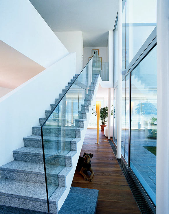 The steel entry door leads to the central hall of the house where the staircase with glass banisters is located.