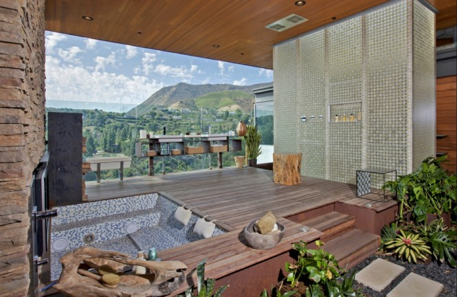This home achieves a wonderful mix of appreciation for natural beauty and a love of modern décor. With the indoor areas flowing seamlessly into the outdoors, and areas of the house offering up expansive glass floors, the structure has a beautifully open air feel.