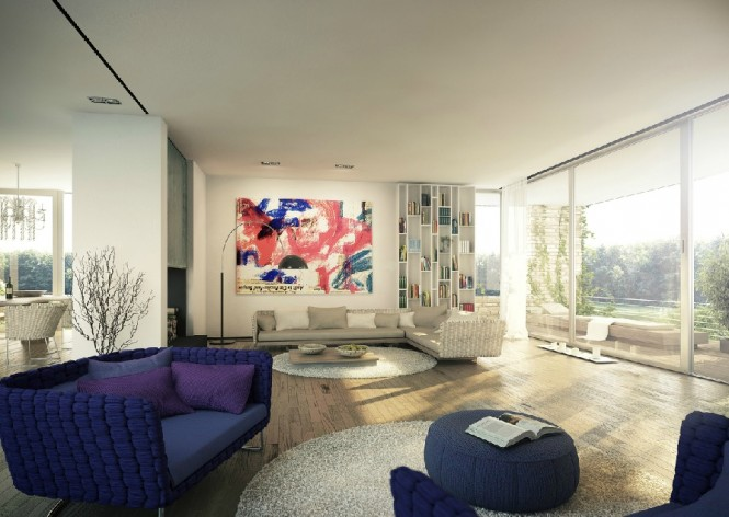 A vast living room houses blue knitted furniture and coordinating modern art, and floor to ceiling bookshelves are filled with colorful entries. Circular rugs pick out two different seating areas on the large floor space, breaking the room into useful segments. An entire wall of glass looks out onto a garden view.