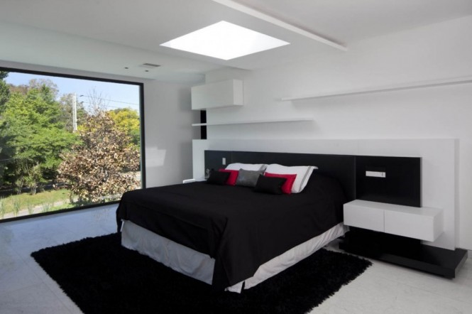 A monochrome contemporary bedroom is lifted with a splash of red.