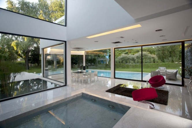 One of the three dining areas of this home floats in the stark white living space, where diners can enjoy the garden and pool views, whilst a lounge area with modern chairs in a warm pop of red provides an area to retire and enjoy the interior waterfall as the evening draws in.