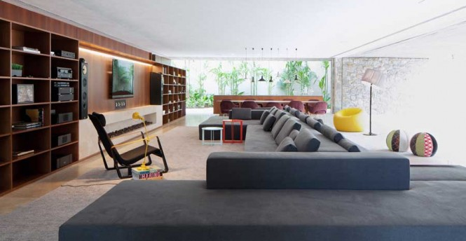 A colossal bespoke sofa divides the room, with one side facing in toward TV and fireplace, and the other firmly facing the patio and pool.