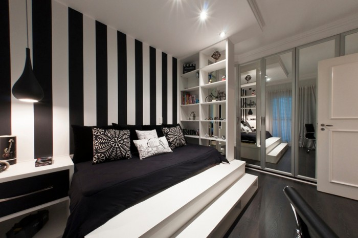 We're also seeing a continuing trend in wide stripe treatments for walls, with emphasis on the monochrome theme, take this bedroom for example; we love these gutsy black and white lines that create an extended headboard feature on one wall. The head of the bed is the perfect place to make a statement in a bedroom, you can be daring and create dazzling impact, but the stimulating design will be out of your eye line when you are trying to relax! The linear pattern is also picked up in the steps at the foot of the bed, which create a lovely grand feeling, and the original placement of the very practical open shelving system to the bedside.