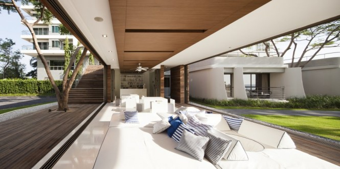 An overhead wooden ceiling panel spans the 14 meter length, giving a framing effect on the sparkling seascape, which can also be enjoyed under the sky from a roof deck or from the modern, abstract form of the stepped landscaping designed by Sanitas Studio.
