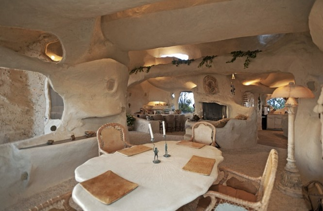 The cavernous living and dining room houses a cozy seating area around a wood burning fireplace with a nearby home bar, an intimate setting which is enhanced by the interesting vaulted ceilings overhead.