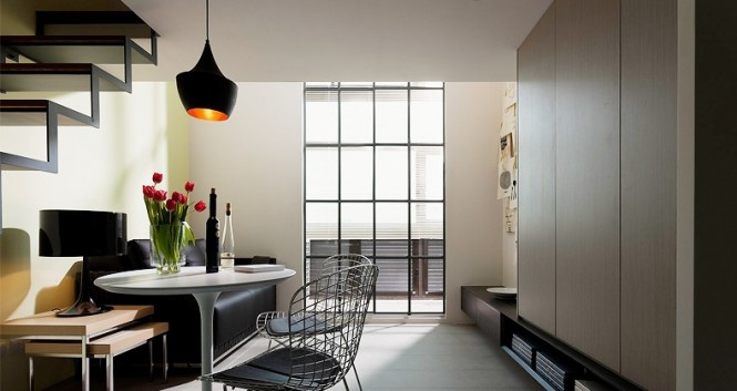 A floating staircase, framed out in black, acts as a piece of graphic art in this simplistic layout; its see-through features are emphasized by the introduction of complimentary wire frame backed dining chairs with the same design element, and mirrored by a floating cabinet.