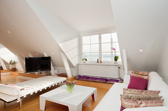 The sloping ceilings are lifted with white whilst the eye is drawn down to a colourful sprinkling of cushions and rugs.