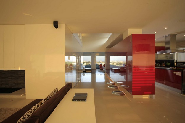The kitchen is partially screened from the lounge area beyond a stretch of bright red units, whilst a run of white cabinets separates the hallway stairs and elevator. A second elevator was intended for the finished project, but instead, a cloakroom was created with a glass floor that looks straight down the 15-story drop!