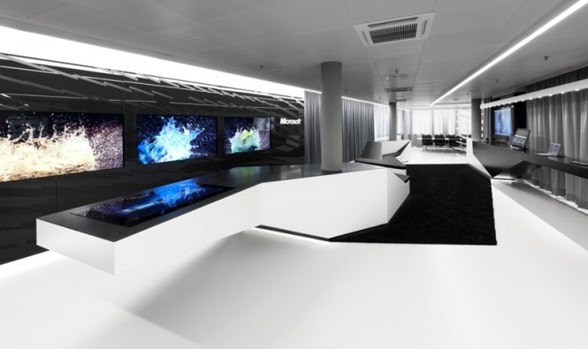 At the far end, a huge meeting table stands equipped for much larger meetings, seating a total of twenty people.