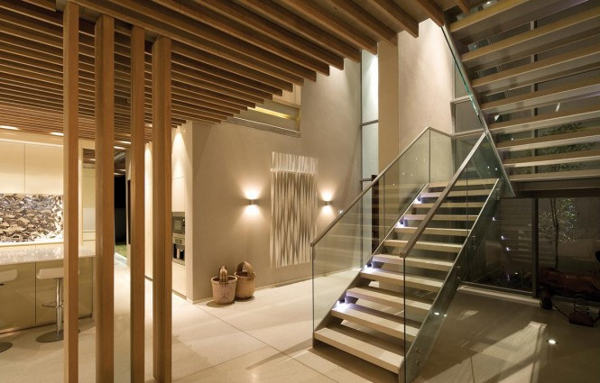 In addition to the retractable doors, lots of glass has been used throughout the interior design to allow light to flow and reflect, it is seen as staircase and mezzanine walkway balustrades, and as a contemporary wall treatment in the bathroom.