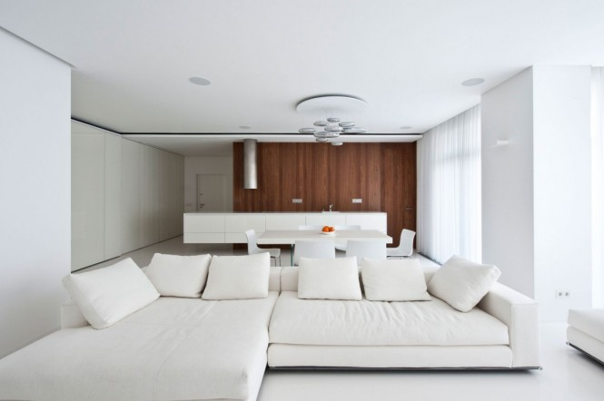 In the lounge area, a long low level sofa reflects the white run of kitchen base units in the background.