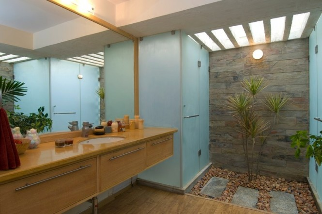 This bathroom sees the introduction of an interior courtyard to add a splice of nature, and promote a sense of calm, when bathing. A large mirror spans the space to help reflect the natural light from the skylight around the entire room, whilst the color palette is reminiscent of a soothing beach scene.