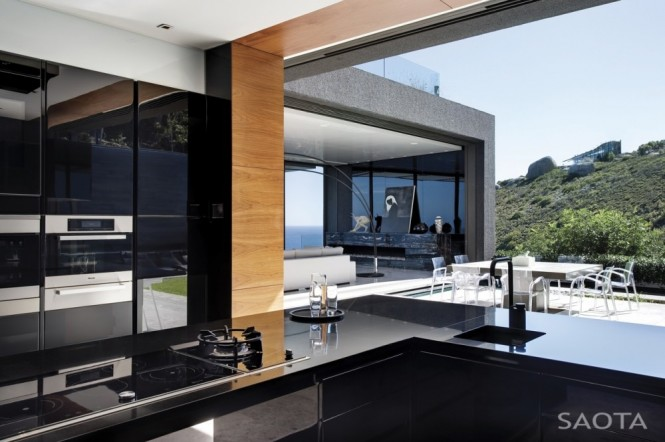 A glossy black kitchen forms a solid base note at the heart of the lightly decorated home, creating a sumptuous cooking zone full of drama and sophistication, a superb area to show off ones serious culinary skills to a gathering of discerning guests.