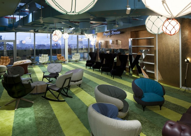 The interior communal areas have been furnished in a fun style, reminiscent of cozy living rooms, complete with high-backed armchairs, scattered pillows and woolen pouffes in the rainbow of Google corporate colors, and clusters of small rocking chairs.