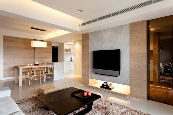 Each room is decked out in a neutral palette, with wood tones creating the only color against a gallery white backdrop, aside from a flash of dove gray behind the home entertainment area. Much of the wood paneling are a fascia to concealed storage areas that keep the apartment looking well organized and uncluttered, though some of the veneer is purely cosmetic, providing warmth and intrigue.