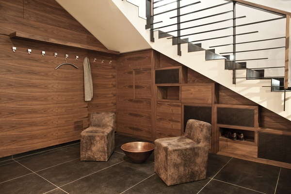 The natural décor begins in the hallway with an expanse of wooden storage units built into the staircase to provide spacious cubbies for shoes and other accessories, as well as wall hanging space for jackets and overcoats. A smart seating area is also provided here for perching on whilst lacing up those shoes, or for callers to wait on.