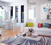 Large edgy artwork adorns the gallery white walls, picking up on the homes colorful accessories, such as an extensive book collection and a rainbow of scatter cushions on the sofa.