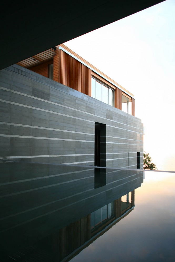 A reflection pond is shadowed by the living span above to form a calming threshold between the entry forecourt and the cool expanse of ocean that stretches beyond. Adjacent wall cladding plays off the horizon of the sea with long runs of horizontal limestone and striped jointing.