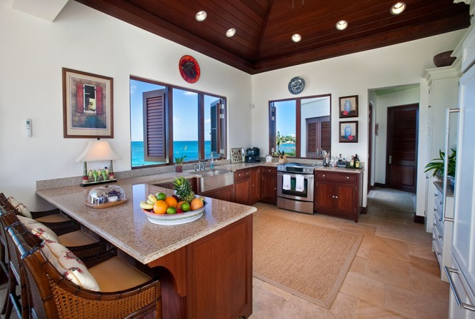 On the opposite side of the holiday hideaway, a kitchen with breakfast bar and an inside dining area are pierced with ever-present ocean panorama via large windows and french doors.