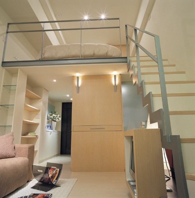 On the opposite side of the hallway storage, a tall lounge cupboard sandwiches a pullout desktop that is easily concealed when not in use for study or dining purposes. On the mezzanine, a small bedroom space feels airy and light on its high perch.