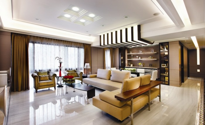 The furniture holds simple lines within the smooth walls that lie beyond the ornately patterned floor of the entryway.