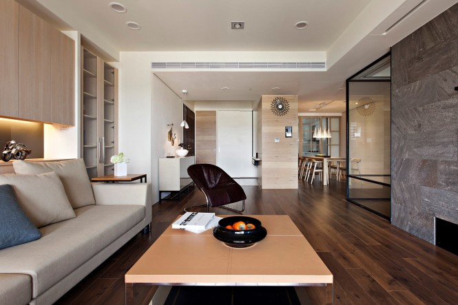 By maintaining a continuous color palette of browns and creams throughout the scheme, each zone melts seamlessly into the next once the glazed doors are drawn back; the same wood flooring has also been installed from edge to edge of this dwelling to further blur the boundaries.