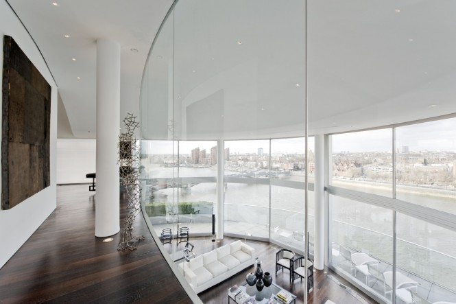 A glass staircase leads up to a sprawling, glass walled mezzanine level that overlooks both the open plan apartment and more of the amazing river and city views below.