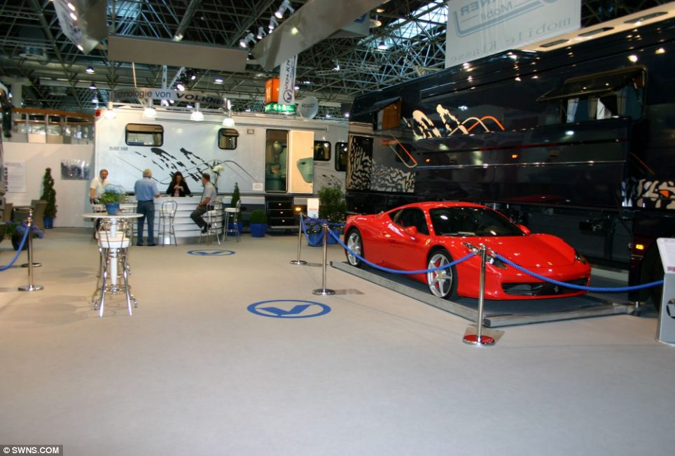 The hidden 'garage' is nestled between the front and rear wheels of the vehicle, and is designed to accommodate a low riding sports car such as a Lamborghini or Ferrari. The access door to the cool compartment opens easily at the press of a button situated on a side panel that causes the hatch to open and the cargo floor to drop to ground level to allow the car to be loaded.