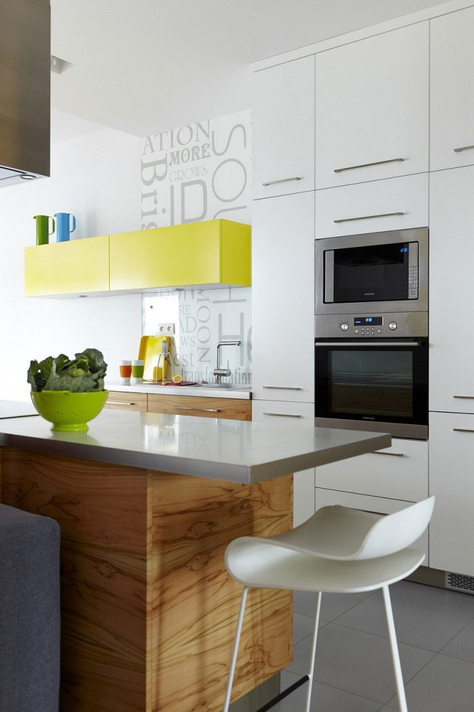 Against a predominantly white backdrop, a trail of comprehensive color dapples the interior in various forms and functions; for example, in the kitchen we see a yellow wall cabinet that follows on the yellow interior of a bookcase and the throw rug in the living room, along with other scattered accessories.
