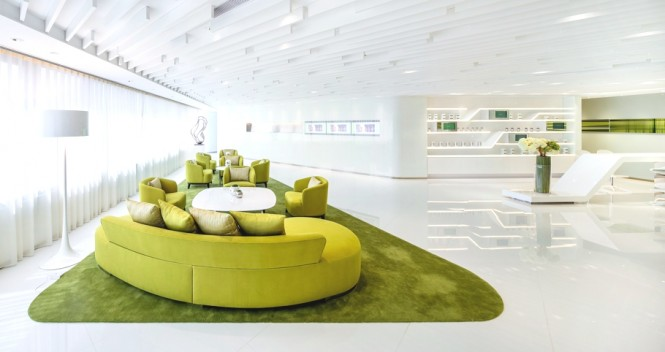 The ceiling holds a series of white beams of varying lengths to create architectural lines above a lime-on-lime reception area that has been designed to emphasize the young and rejuvenated brand essence. The fabric sofas have been designed with soft, rounded edges to appear inviting and welcoming to customers.