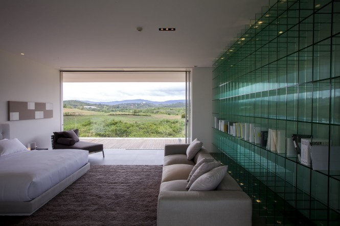 The modern bedroom offers an unusual solution for bookshelves in the form of an entire wall of sectioned glass, which also compliments the glass of the exterior walls.