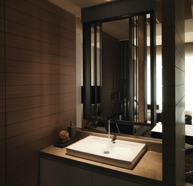 Further accentuating the linearity of this home, the washroom is also inclusive of the full woodwork that lines the walls throughout the rest of the living spaces. This unique washbasin has a see through wall that looks beyond the sink into a sitting area that is flooded with natural light.