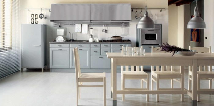A retro kitchen is subdued in matte grey paint that resembles primer yet looks quite at home accented by the cream walls and natural finished furniture.