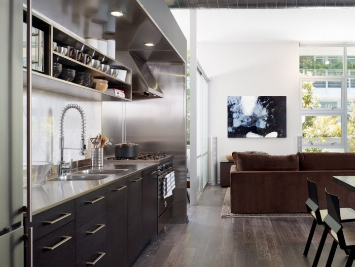 The young single male's open floor plan kitchen/dining/living space gets a shot of high dose of masculinity with industrial strength materials such as stainless steel, graphite cabinets and rustic wood floors.