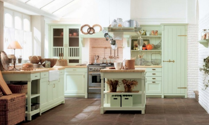The mint green we see in this kitchen  is quite feminine. While all of the furniture is accented in a farmhouse style with open shelving, paneled doors and brass hardware.