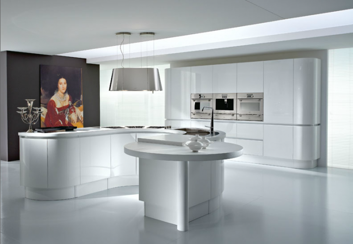 This stunning modern island is as artistic as the portrait hanging beside it. Its curvy lines and sculpted appearance are aesthetically pleasing while its work surface, cooking station and gathering space are functionally attractive.