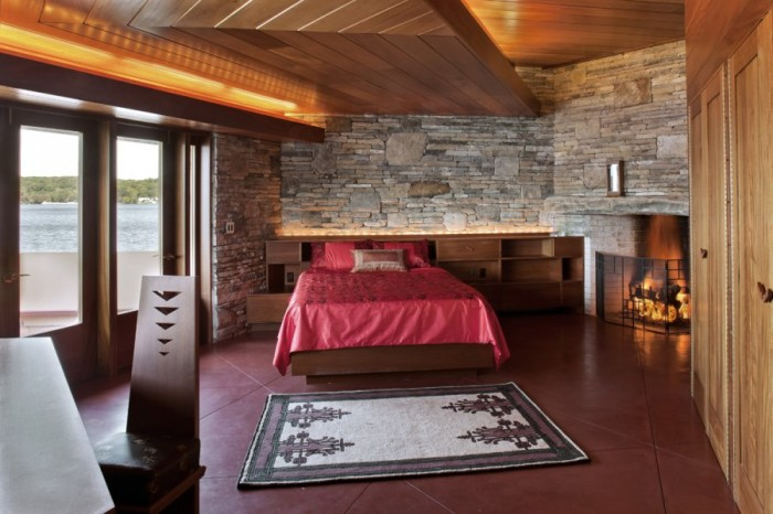The master bedroom  features a rich wood, offset chevron ceiling design lit from above. It anchors itself into a rugged rock wall at the back of the room.