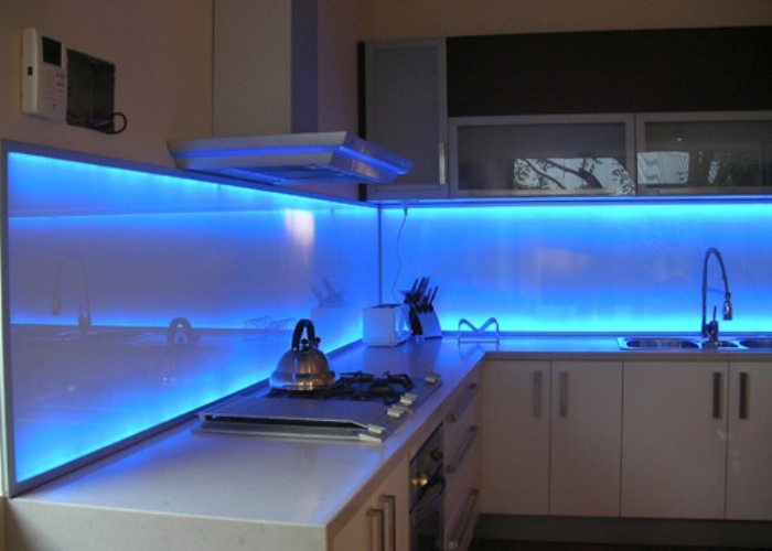 Brilliant blue LED lights add a stunning effect to this glass backsplash.