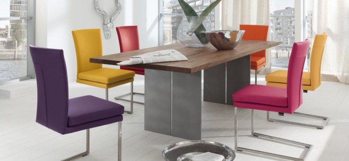 Hard-edged elements like this modern steel dining table can easily be softened and warmed by adding color through brightly multi-hued chairs for a contemporary modern style.