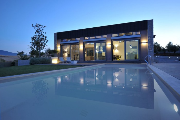 A luxuriously large swimming pool expands from just outside the home outwards.